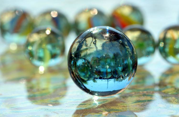 A ball of glass will bounce higher than a ball of rubber. A ball of solid steel will bounce higher than one made entirely of glass.